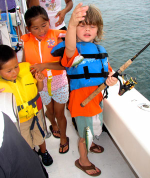 A group of kids enjoying their fishing trip out on the water.